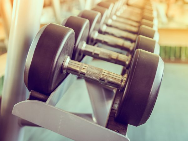 dumbbell in gym – vintage effect and sun flare filter effect